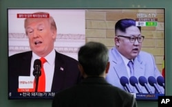 FILE - A man watches a TV screen showing file footages of U.S. President Donald Trump, left, and North Korean leader Kim Jong Un during a news program at the Seoul Railway Station in Seoul, South Korea, March 27, 2018.