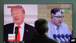 FILE - A man watches a TV screen showing file footages of U.S. President Donald Trump (L) and North Korean leader Kim Jong Un (R) during a news program at the Seoul Railway Station in Seoul, South Korea, March 27, 2018.