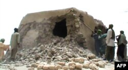 FILE - This file photo taken on July 1, 2012 shows a still from a video of Islamist militants destroying an ancient shrine in Timbuktu.