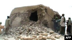 FILE - This file photo taken on July 1, 2012 shows a still from a video of Islamist militants destroying an ancient shrine in Timbuktu. The trial of a Malian jihadist charged with war crimes for ordering the 2012 destruction of 14 mausoleums of Muslim sai