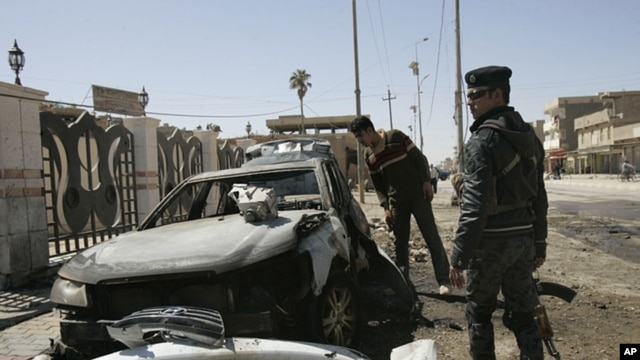 An Iraqi policeman stands guard at the site of a bomb attack in Ramadi, 100 km (60 miles) west of Baghdad, March 20, 2012.