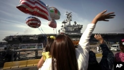 In this Oct. 1, 2015 file photo, family members of sailors wave as the U.S. Navy aircraft carrier USS Ronald Reagan arrives at a U.S. Navy base in Yokosuka, Japan south of Tokyo. (AP Photo/Eugene Hoshiko, File)