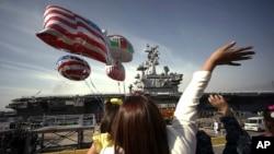 ARSIP – Dalam foto yang diambil tanggal 1 Oktober 2015, anggota keluarga para pelaut melambaikan tangan ke arah kapal induk AL AS, USS Ronald Reagan, yang tiba di pangkalan AL AS di Yokosuka, Jepang sebelah selatan Tokyo (foto: AP Photo/Eugene Hoshiko, Arsip)