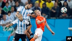 Netherlands' Dirk Kuyt goes for a header with Argentina's Javier Mascherano and Ezequiel Garay during the World Cup semifinal soccer match in Sao Paulo, Brazil, July 2014. (AP Photo/Frank Augstein)