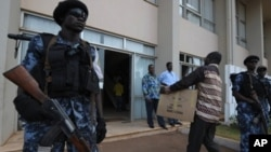 Togolese police forces stand guard at gate as electoral Commission members arrives with the ballot result papers on March 6, 2010 in Lome ahead of an election results announcement.