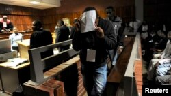 South African police officers arrested on suspicion of murder appear for bail hearing east of Johannesburg on March 11, 2013. Nine South African policemen pleaded not guilty to charges of murdering a Mozambican taxi driver who has handcuffed and dragged behind a police vehicle.