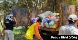 Petugas menaikkan sampah plastik dan popok ke atas bak truk di kawasan Wringinanom, Gresik (Foto: VOA/ Petrus Riski).