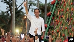 In this file photo, Indonesian president-elect Joko Widodo greets supporters during a gathering in Jakarta, Wednesday, July 23, 2014.