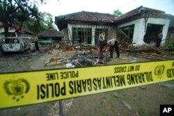 Polisi memeriksa rumah pengikut Ahmadiyah yang rusak setelah diserang sekelompok orang di Pandeglang, Banten, 7 Februari 2011. (Foto: AP)