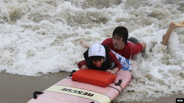 Austin Bramson takes a ride on a surfboard with the help of a Best Day at the Beach volunteer. (VOA/D. Grunebaum)