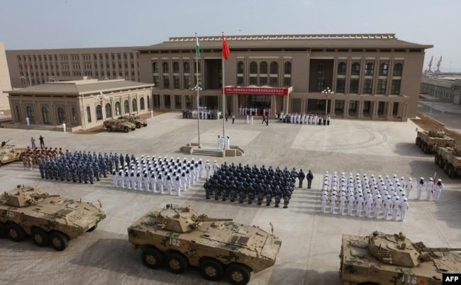 """中國人民解放軍人員參加吉布提中國軍事基地開幕式。 這是中國第一個海外海軍基地,是中國擴大其國外軍事存在的重要一步(2017年8月1日)。 地緣情報分析公司斯特拉福(Strarfor)的在線刊物""""斯特拉福世界觀""""(Stratfor Worldview)和衛星圖像分析公司""""全資源分析""""(Allsource Analysis)提供的兩張圖像顯示,中國在吉布提的基地有三層安全防禦,戒備森嚴。 斯特拉福公司分析,這處基地有大約23000平方米的地下空間。 該基地距離美軍在吉布提的駐軍總部只有八英里遠,美國在吉布提的駐軍有4500人。 此外,日本、法國、英國等國在吉布提也有駐軍。"""