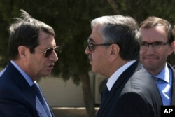 FILE - Cypriot President Nicos Anastasiades, left, and breakaway Turkish Cypriot leader Mustafa Akinci, right, talk at the disused Nicosia airport inside a United Nations controlled buffer zone in this divided island of Cyprus, Sept. 14 2016.