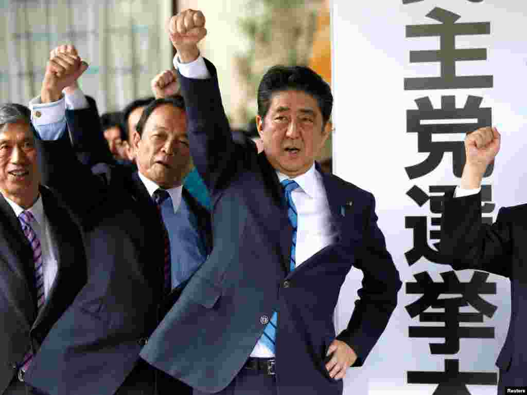 Japan's Prime Minister Shinzo Abe (3rd L) and his party's lawmakers raise their fists as they pledge to win in the upcoming lower house election, at their party headquarters in Tokyo.