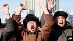 Norcoreanos celebran el lanzamiento de un misil intercontinental durante una transmisión de televisión en la que se hizo el anuncio en Pyongyang.