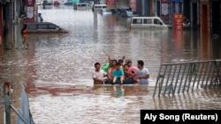 Children sit on a makeshift raft on a flooded road following heavy rainfall in Zhengzhou, Henan province, China July 22, 2021.