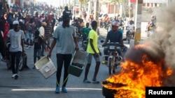 Manifestan ki te rasanble dèyè yon barikad pandan yo t ap pwoteste kont gouvènman Preidan Jovenel Moise la.