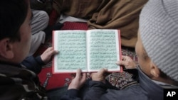 "Afghans jointly read Islam's holy book ""Quran"" during a celebration to mark the anniversary birthday of Islam's Prophet Mohammad at a mosque in Kabul, Afghanistan, February 4, 2012."