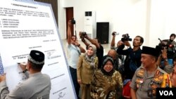 Forum Komunikasi Pimpinan Daerah Kota Surabaya menandatangani pernyataan sikap tidak takut melawan intoleransi, radikalisme dan terorisme, serta jogo Suroboyo, di Mapolrestabes Surabaya, Selasa (14/5). (Foto: VOA/Petrus)