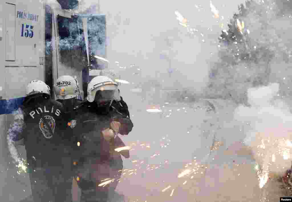 Riot police take cover as protesters use fireworks against them during a demonstration against the opening of a new road including a part of the Middle East Technical University campus in Ankara, Turkey.