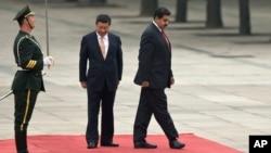 El presidente chino Xi Jinping, centro, y el mandatario venezolano Nicolás Maduro, ajustan el paso durante la revista a la guardia de honor en Beijing.