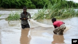 FILE - Children work to salvage goods washed away by floodwaters in the southern district of Chikwawa, near Blantyre, Malawi, Jan, 15, 2015.