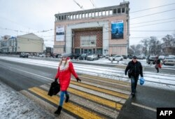 """Pedestrians walk outside the 1938 Rodina (""""Motherland"""") cinema in northern Moscow, Dec. 13, 2018."""
