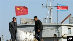 FILE - North Korean men stand on a boat used for trade between China and North Korea on the waterfront at the North Korean town of Sinuiju, opposite the Chinese border city of Dandong, Oct. 11, 2006.