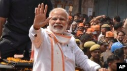 Indian Prime Minister Narendra Modi waves to supporters as he campaigns for his party in the Uttar Pradesh state elections in Varanasi, India, March 4, 2017. Uttar Pradesh and four other Indian states are having state legislature elections in February-Mar