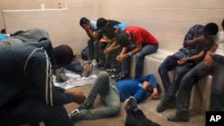 Immigrants, who have been caught crossing the border illegally, are housed inside the McAllen Border Patrol Station in McAllen, Texas where they are processed, July 15, 2014.