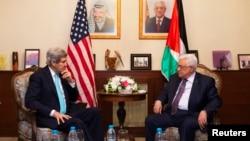 Menlu AS John Kerry (kiri) saat bertemu Presiden Palestina Mahmoud Abbas di Amman, Yordania (26/3).