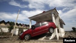 A car damaged by floods is seen after heavy rainfalls hit Zhou Kou Dian Village, Fangshan district, near Beijing, China, July 22, 2012.
