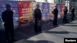 携带防暴装备的警察在新疆法院附近的检查站站岗,从9月17日开始,该法院开始审理伊力哈木的案子。