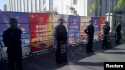 Policemen in riot gear guard a checkpoint on a road near a courthouse where ethnic Uighur academic Ilham Tohti's trial is taking place in Urumqi, Xinjiang Uighur Autonomous Region, Sept. 17, 2014.