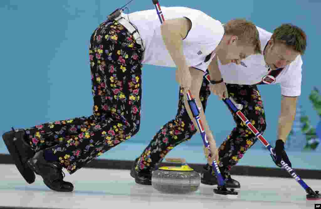 Norway's Haavard Vad Petersson and Torger Nergaard sweep ahead of the rock during men's curling competition against Canada at the 2014 Winter Olympics, Feb. 14, 2014.