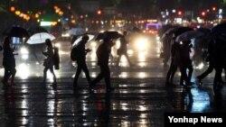 한반도가 태풍 '노을'의 간접 영향권에 든 가운데, 11일 서울 광화문 앞에 우산을 쓴 시민들이 걸어가고 있다.