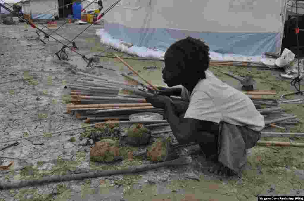 A young girl rubs sticks together to try to start a fire. The girl is one of thousands of people who have sought protection inside the UNMISS base in Malakal.