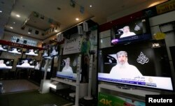 FILE - Nasr al-Ansi, a leader of the Yemeni branch of al-Qaida in the Arabian Peninsula, is shown on televisions at a shop, delivering a message in which AQAP claims responsibility for the attack on the French magazine Charlie Hebdo, in Sana'a, Yemen, Jan. 14, 2015.