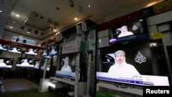 Nasr al-Ansi, a leader of the Yemeni branch of al-Qaida (AQAP), is shown on televisions in at a shop in Sana'a, Yemen, stating that AQAP claims responsibility for the attack on Charlie Hebdo last week.