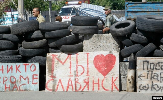 Pro-Russian separatists stand guard at a checkpoint, where a sigh reads