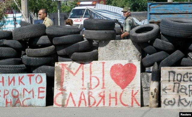 "Pro-Russian separatists stand guard at a checkpoint, where a sigh reads ""We love Slovyansk,"" in the eastern city of Slovyansk, Ukraine, July 1, 2014."