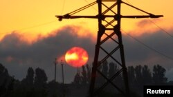 FILE - An electricity transmission tower is seen on the outskirts of the town of Lozova, some 450 km (280 miles) east of Ukraine's capital Kyiv, Aug. 28, 2008. Ukraine is investigating a suspected cyberattack on Kyiv's power grid over the weekend.
