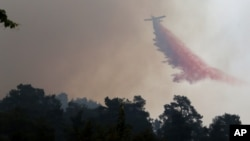 Fire retardant is dropped on a huge forest fire that continues to rage out of control for a third day, in the mountainous areas southwest of Cyprus' capital Nicosia, June 21, 2016.