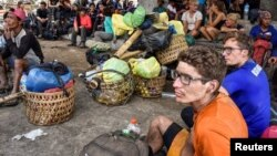 Người leo núi nước ngoài và Indonesia ngồi nghỉ ở làng Sembalun khi tìm đường xuống núi Rinjani hôm 29/7.
