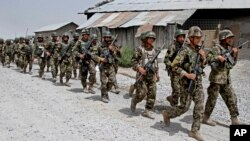 Afghan National Army soldiers march in Sangin district of Kandahar province southern Afghanistan, June 13, 2013.