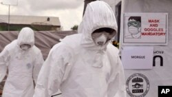 FILE - Health workers are seen wearing Ebola protective gear at an Ebola treatment center at Tubmanburg on the outskirts of Monrovia, Liberia, Nov. 28, 2014.