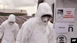 FILE - Health workers wearing Ebola protective gear work at an Ebola treatment center at Tubmanburg on the outskirts of Monrovia, Liberia, Nov. 28, 2014.