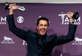 Luke Bryan poses with his awards for entertainer of the year and vocal event of the year at the 48th ACM Awards in Las Vegas, April 7, 2013.