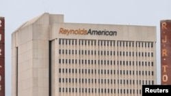 FILE - The headquarters of Reynolds American is seen next to the old R.J. Reynolds Tobacco smoke stacks from a previous manufacturing plant in downtown Winston-Salem, North Carolina, May 23, 2014.