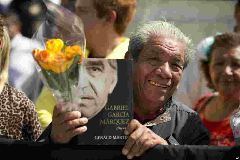 Seorang penggemar memegang bunga dan tandatangan Gabriel Garcia Marquez saat menunggu di luar Palace of Fine Arts di Mexico City, untuk memberi penghormatan pada penulis yang banyak dicintai itu (21/4). (AP/Rebecca Blackwell)