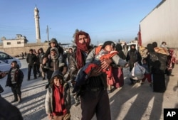 FILE - Syrians gather at the Bab al-Salam border gate with Turkey, in Syria, Feb. 6, 2016. Thousands of Syrians have rushed toward the Turkish border, fleeing fierce Syrian government offensives and intense Russian airstrikes.